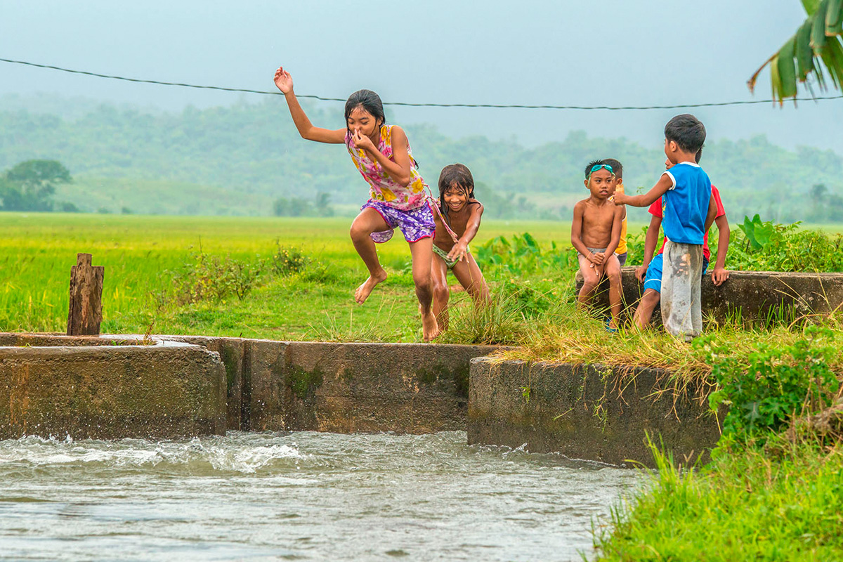 Philippines, children playing at water channel