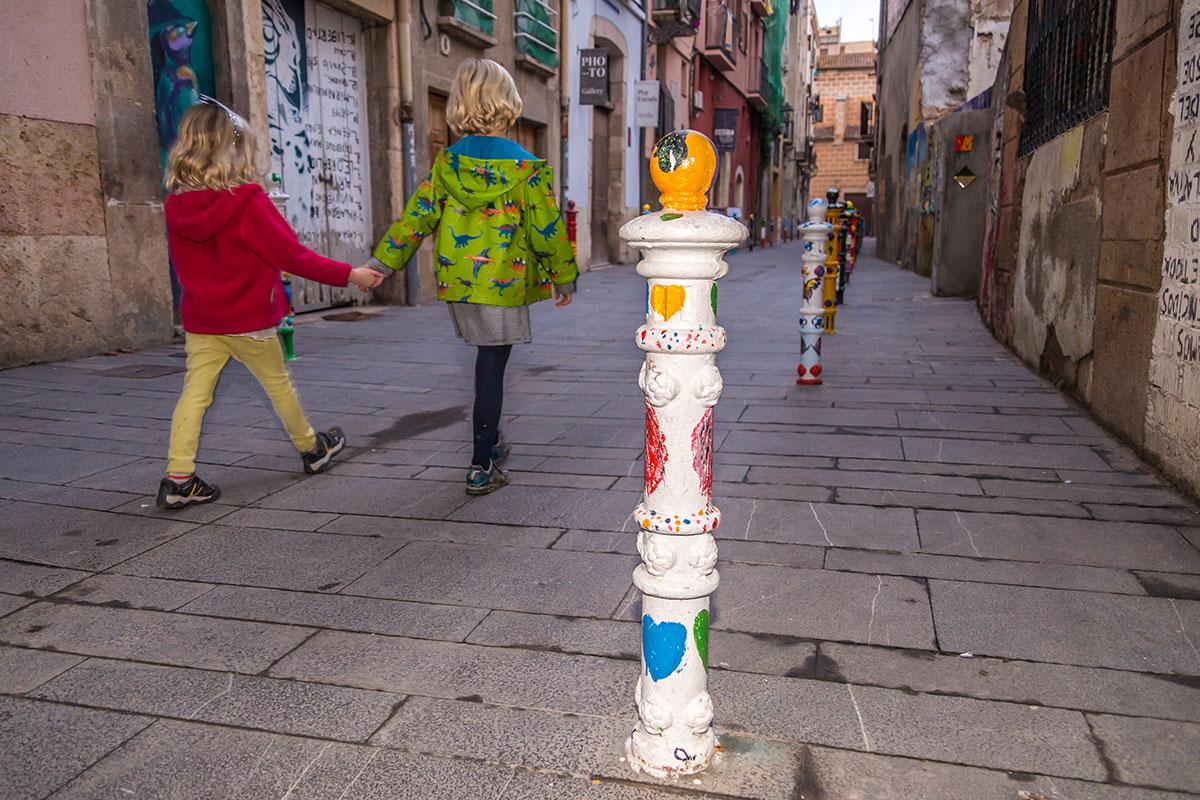 Spanien, Katalonien, Tarragona, Gasse mit bemalten Pfählen und Kindern