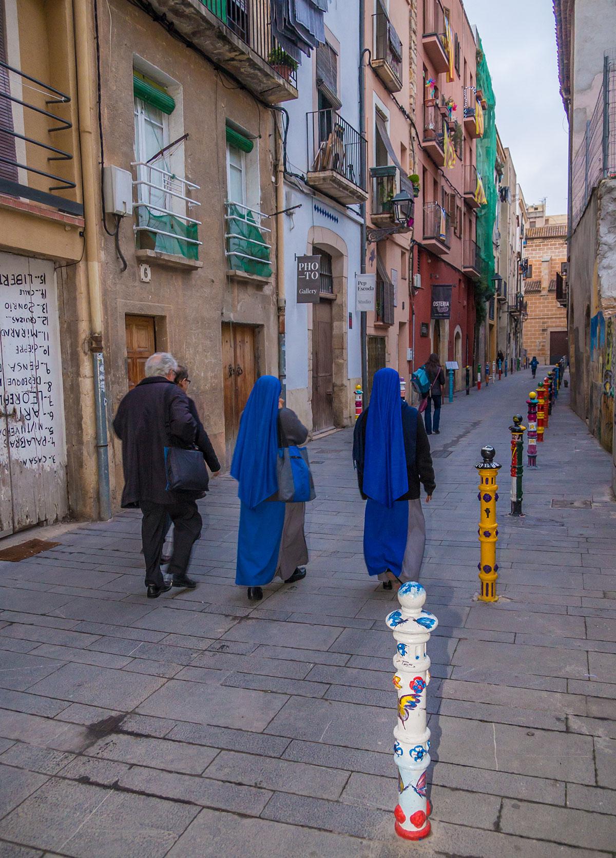 Spanien, Katalonien, Tarragona, Gasse mit bemalten Pfählen und Nonnen