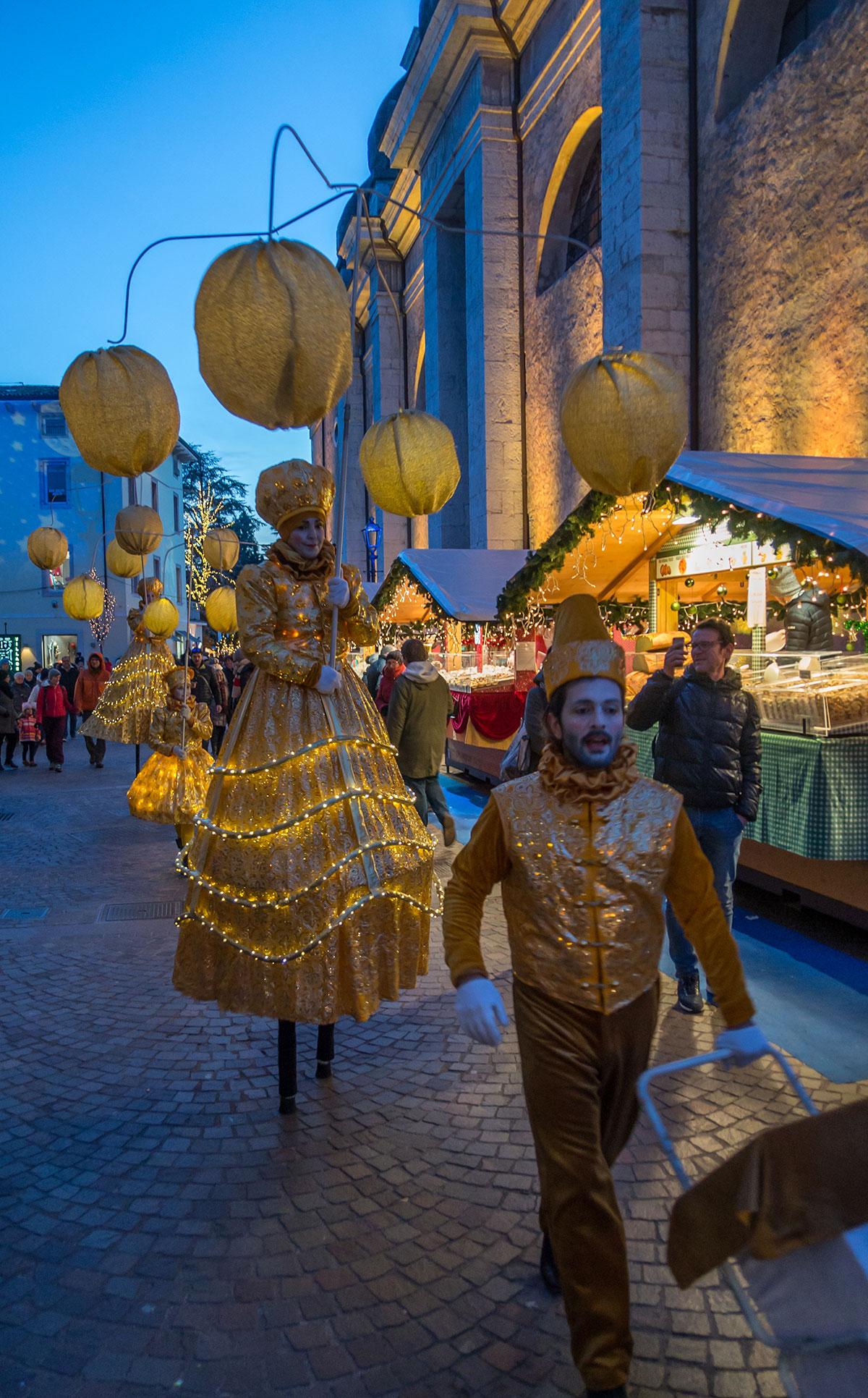Weihnachtsmarkt in Arco mit Stelzen Läufern und Lampions